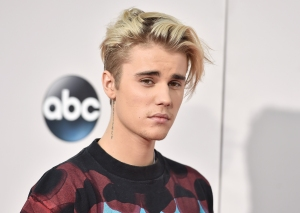 """FILE - In this Sunday, Nov. 22, 2015 file photo, Justin Bieber arrives at the American Music Awards at the Microsoft Theater in Los Angeles. With his recent batch of hit singles and semi-grown-up sound  - including the electro-pop """"Where Are U Now"""" with DJ-producers Skrillex and Diplo - adult men have begun attending the church of Bieber, and while some have issues admitting it, other proudly say they are Beliebers. """"Sorry"""" and """"What Do You Mean,"""" currently at Nos. 2 and 4 on Billboard's Hot 100 chart, helped Bieber solidify his comeback after years of a broken image, which included arrests, public smoking and fainting onstage that led to hospitalization. (Photo by Jordan Strauss/Invision/AP, File)"""