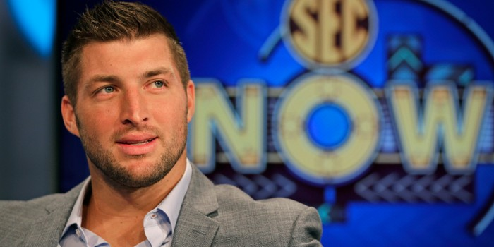 Tim Tebow ponders a question during an interview on the set of ESPN's new SEC Network in Charlotte, N.C., Wednesday, Aug. 6, 2014. Tebow has a new job as a commentator for the SEC Network, but is still looking for work in the NFL as a quarterback. (AP Photo/Chuck Burton)