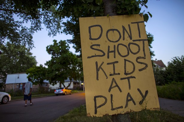 A man walks down a street past a handmade sign posted in the Englewood neighborhood in Chicago, Illinois, United States, July 29, 2015. Residents put the signs up in the area which has a high level of gun violence in hopes of reducing crime. REUTERS/Jim Young   - RTX1MCAH